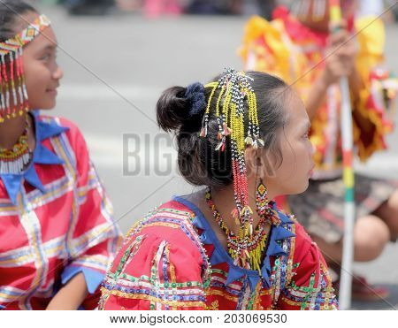 DAVAO CITY, PHILIPPINES--AUGUST 2014: Two girls in ethnic costumes and beaded headdress at the street dancing parade. Kadayawan is celebrated August each year to give thanks for an abundant harvest.