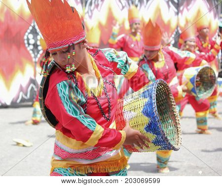DAVAO CITY, PHILIPPINES--AUGUST 2014: Participants dancing with colorful baskets and costumes at the parade. Kadayawan is celebrated August each year to give thanks for life and an abundant harvest.