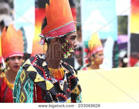 DAVAO CITY, PHILIPPINES--AUGUST 2014: A boy with colorful headdress and ethnic costume at the parade. Kadayawan is celebrated August each year to give thanks for life and an abundant harvest.
