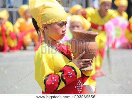 DAVAO CITY, PHILIPPINES--AUGUST 2014:A girl in colorful costume holds a jar for their performance at the parade. Kadayawan is celebrated August each year to give thanks for an abundant harvest.