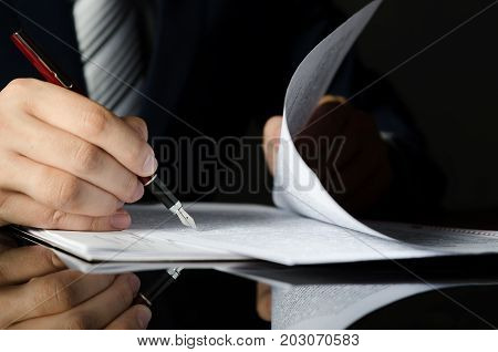 Notary Signing A Contract With Fountain Pen In Dark Room