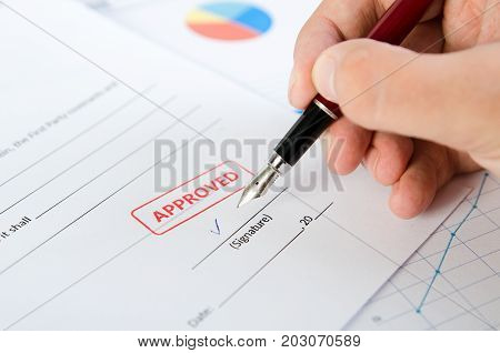 Man Signs The Contract With Pen. Approved Stamp On Document