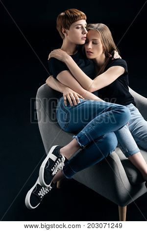 Lesbian Couple Embracing In Armchair