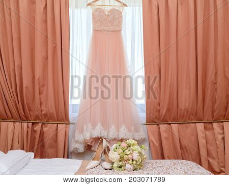 Beautiful Lush Wedding Bouquet Of Pink And White Flowers And Bride's Shoes On Bed With Wedding Dress