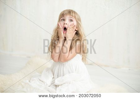 Portrait of pretty little girl in white dress , she is surprised and put her hands on cheeks. She is happy and waiting for a moment.