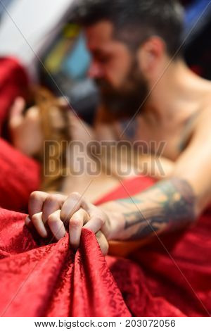 Male And Female Hands Crossed On Red Patterned Sheets