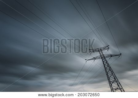 High Voltage Power Lines And Transmission Towers On A Cloudy Day. Poles And Power Lines Silhouettes.
