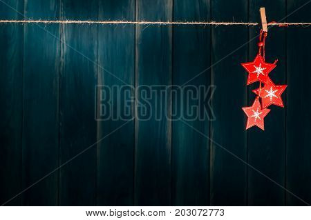 Blue Christmas background with wooden red stars christmas toys hanging on clothespin on grunge wooden wall. Xmas and New Year concept. Christmas or New Year card template with copy space.