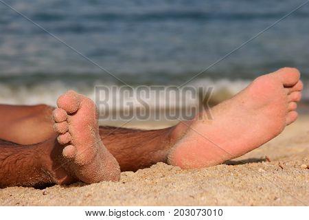 a pair of sandy feet on a sandy beach