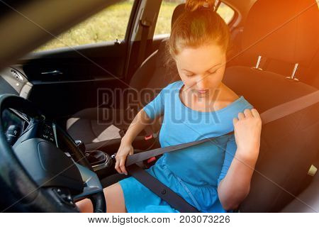 Stylish Girl In Dress In Car Seat Belt For Safety Before Driving. Beautiful Young Woman In Car Faste