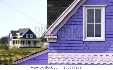 Detail of a traditional, generic style house on Iles de la Madeleine, Quebec. Another colourful wooden house can be seen in the distance. Space for text.