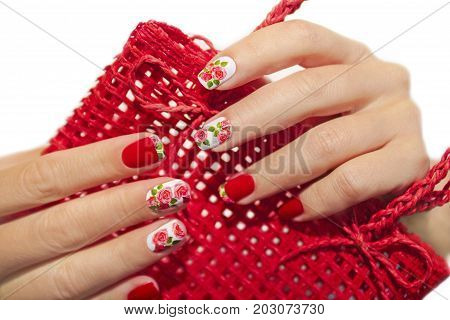 Red French manicure with a design of roses on a white background.