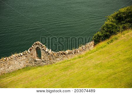 Sea shore, grass covered hill side and old stone wall with window outdoors, Ireland