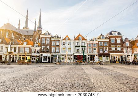 View on the beautiful buildings facades and church on the central square during the sunny morning in Delft city, Netherland