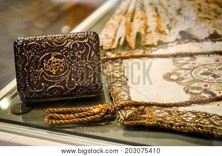 Riga, Latvia - July 5, 2012 - Antique ball accessories with floral decor. Handmade luxury bag with gold braid and embroidery, silver purse with flower monograms and engraving, fan. Early 20th century.