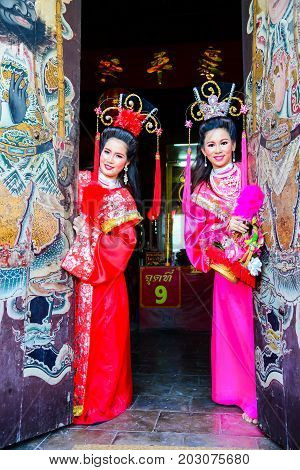 Chachoengsao, Thailand - July 14, 2013 : Beautiful women with traditional chinese dress at Chinese shrine door with painting of ancient soldier in Thailand.