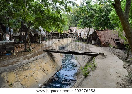 Small sewage canal surmounted by a bridge made of two trunks of trees that crosses the cooperative of sculptures of Mombasa in Kenya
