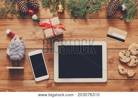 Christmas online shopping background. Mobile and tablet screen with copy space top view on wood, credit card and present boxes. Electronic devices, internet commerce on winter holidays concept