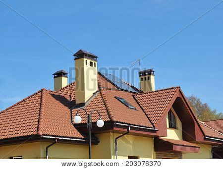 Closeup of solar panel on red tiled house roof with skylights chimney and roof window.