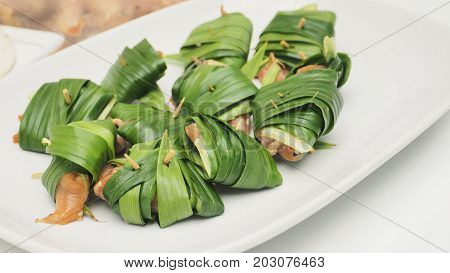 Thai food chicken wrapped in pandan raw step prepare for fried in white plate Macro photo focus select at foreground.