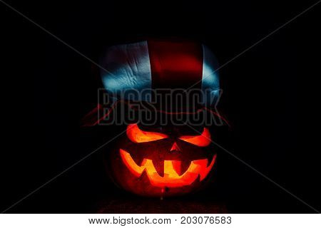 Very Scary Halloween Pumpkin, With A Menacing Glance And A Grinning Villain, In The Dark With A Foot