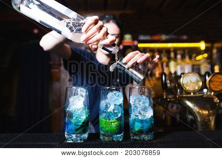 The barman mixes the ingredients of a beautiful blue cocktail. The barman pours alcohol into a cocktail. Alcoholic beverage at the bar.