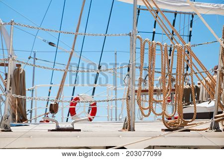 details of large classic style ocean sailing ship equipment against blue sky