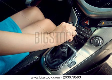 Close Up Of Young Woman Shifting Gears On Gearbox And Driving Car. Closeup Of Female Driver Hand Shi