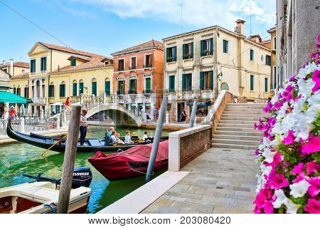 VENICE,ITALY - JULY 25,2017 : Gondola carrying tourists on a small canal sidelined by coloful old buildings and flowers