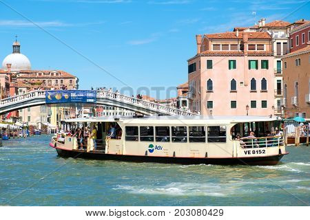 VENICE,ITALY - JULY 25,2017 : A vaporetto sails below the Ponte degli Scalzi on the Grand Canal in Venice