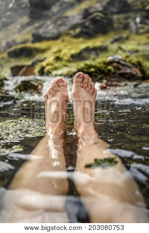 Woman bathing in a hot spring in Iceland in the Landmannalaugar mountains view of the feet.