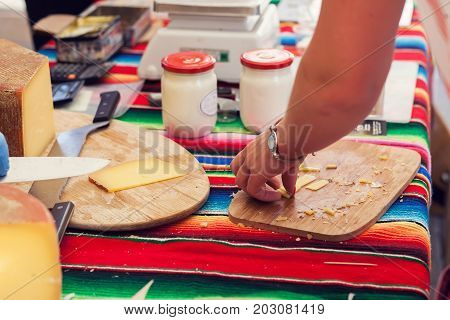 a person cut a cheese in the cheese market