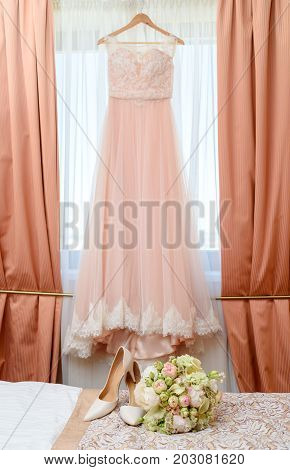 Beautiful lush wedding bouquet of pink and white flowers and bride's shoes on bed with wedding dress on background in bride's bedroom