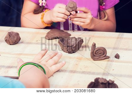 Children molded from clay at the table