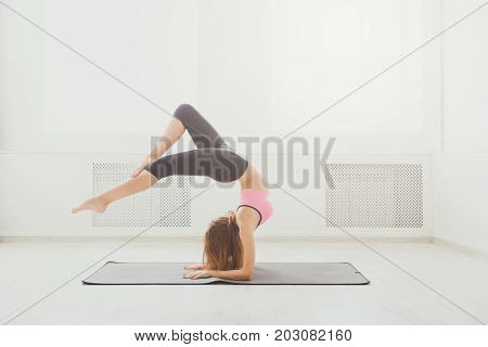 Young attractive woman practicing yoga, standing in headstand pose. Beautiful fitness girl working out indoors, variation of supported headstand, salamba sirsasana, side view.