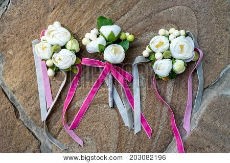 Top view of wedding boutonniere for the groom and bridesmaids on stone background. Wedding details outdoor with copy space. Wedding morning preparation