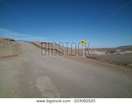 A traffic board on a dirt road in the middle of Atacama Desert, Chile, with dunes on the back