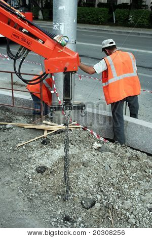 Works on construction of sidewalk.