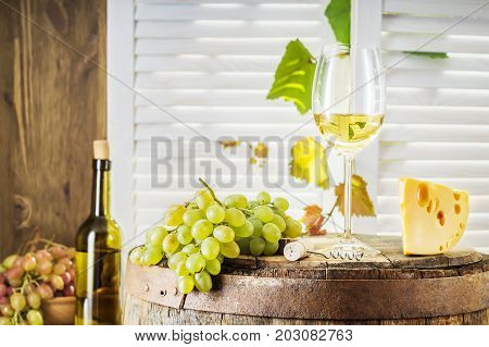 Still life of white wine with wooden keg. Wine bottle glass of white wine with cheese and grape on a old wooden barrel. Wine tasting and production concept.