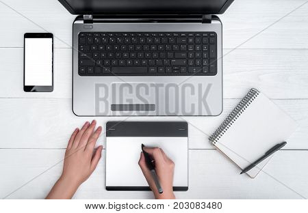 Top view of open laptop computer cell phone empty diary and graphic tablet. Girl's hands with graphic tablet drawing and retouching image on laptop free space. Mobile phone with white screen