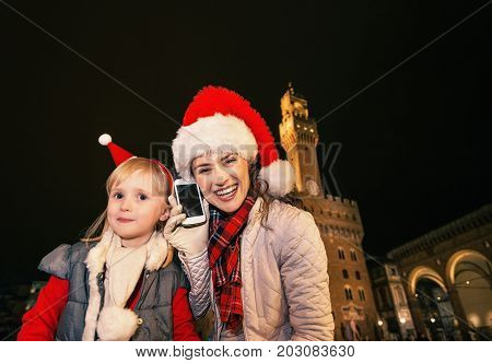 Mother And Child In Christmas Hats Speaking On Cell Phone