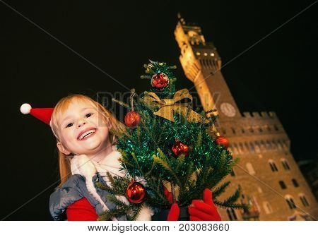 Child Against Palazzo Vecchio In Florence With Christmas Tree