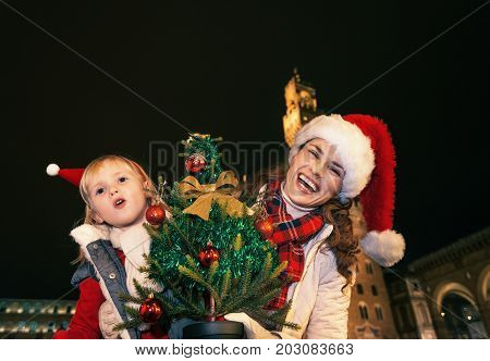 Mother And Child With Christmas Tree Having Fun Time In Florence