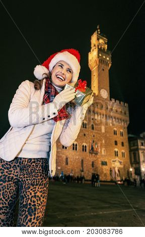 Woman Near Palazzo Vecchio Shaking Christmas Present Box, Italy