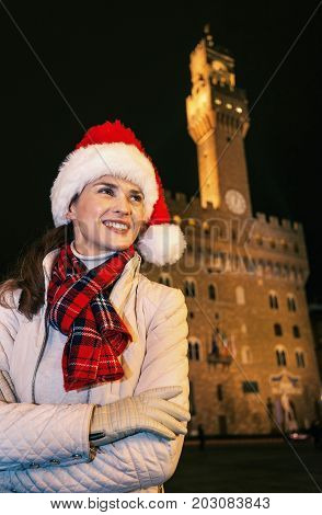 Happy Woman In Christmas Hat Near Palazzo Vecchio Looking Aside