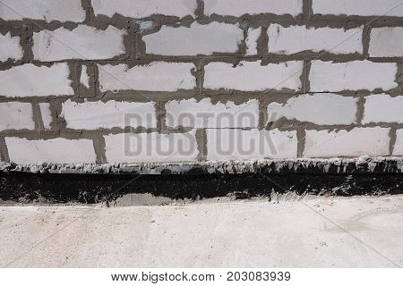 Close up on Important Waterproofing Options for Concrete Foundations. Basement Bitumen Membrane Wall Waterproofing.