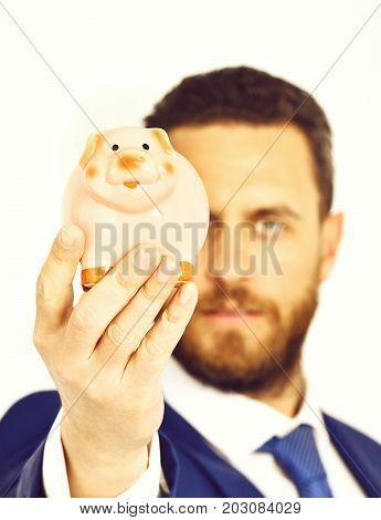 Businessman In Suit And Tie Holding Piggybank