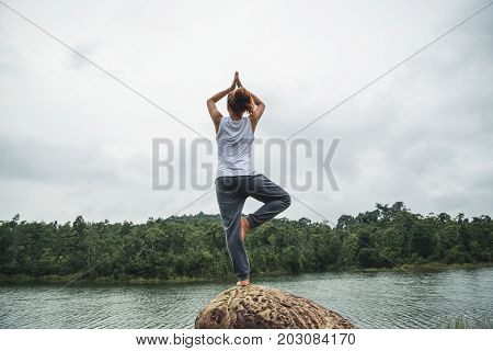 Asian women relax in the holiday. Play if yoga. On the rocks in the middle of the water.