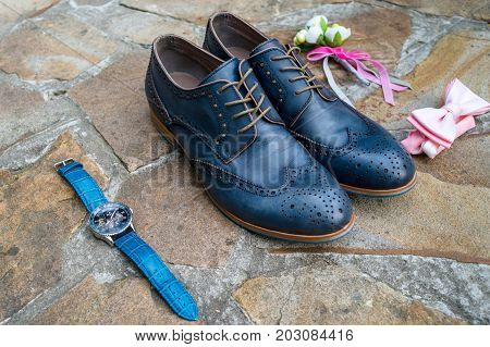 Blue leather groom shoes watches boutonniere and pink bowtie on brown natural stone. Groom wedding accessories. Man watches bow-tie boutonniere and footwear on stone background