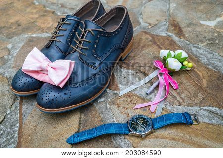 Pink bowtie on blue leather shoes. Blue leather groom shoes watches boutonniere and pink bowtie on brown natural stone. Groom wedding accessories.